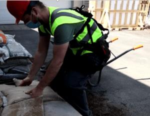 Ouvrier soulevant un sac de sable avec un exosquelette